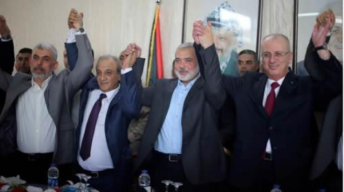 FILE PHOTO; Palestinian Prime Minister Rami Hamdallah (R) and Hamas Chief Ismail Haniyeh hold hands in Gaza City October 2, 2017.