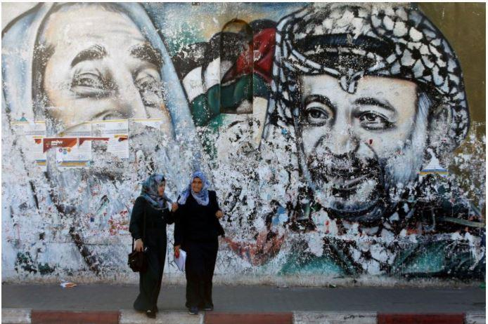 Palestinian students stand in front of a mural depicting late Hamas leader Ahmed Yassin and late Palestinian leader Yasser Arafat, in Gaza City October 12, 2017.