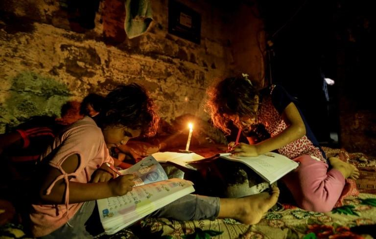 Children do their homework by candlelight during one of the many power cuts that have hit Gaza since the Palestinian Authority reduced payments