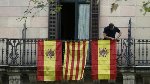 A man hangs Spanish and Catalan flags