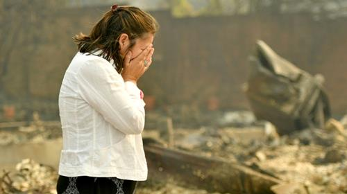 Martha Marquez is overcome as she looks at her burned home in Santa Rosa, California