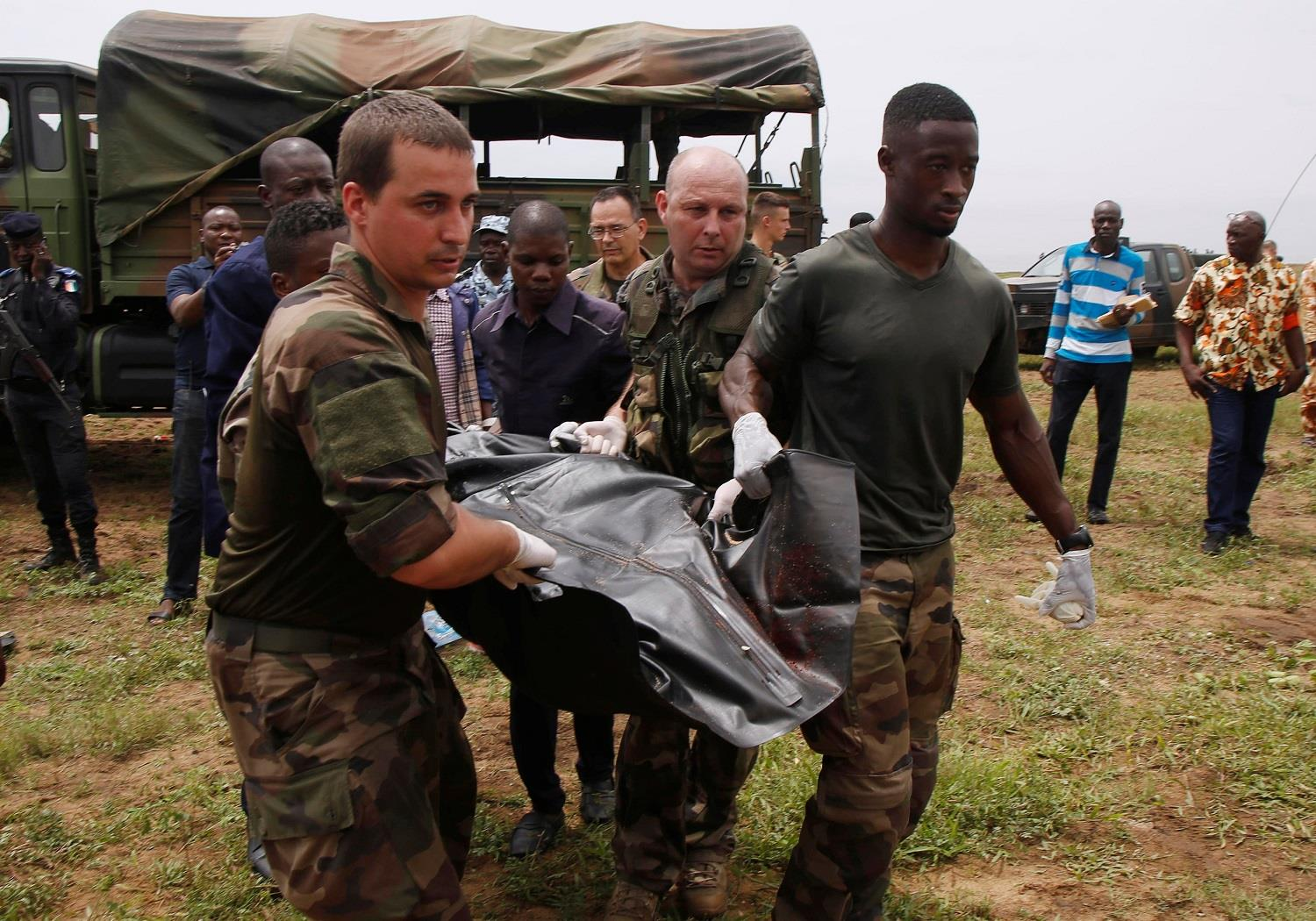 French soldiers and rescuers carry a body after a propeller-engine cargo plane crashed into the sea near the international airport in Ivory Coast's main city, Abidjan.