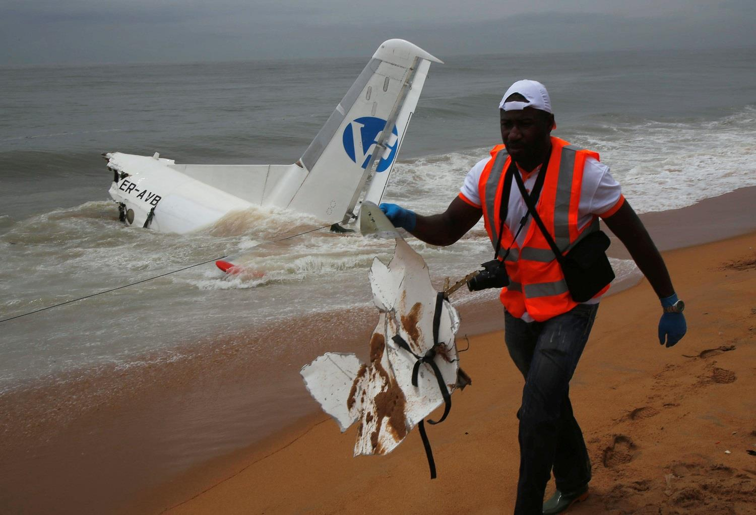 A rescuer carries a piece of a cargo plane after it crashed into the sea near the international airport in Ivory Coast's main city, Abidjan