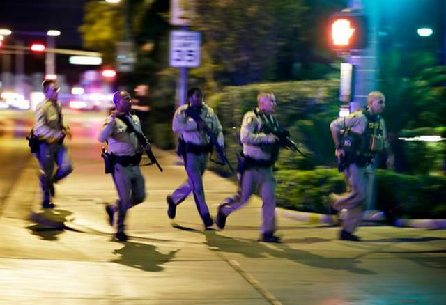 Police run to cover at the scene of a shooting near the Mandalay Bay