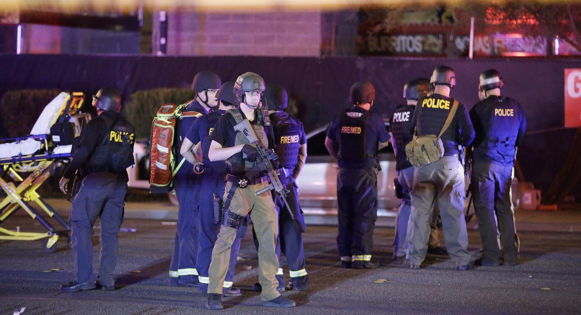 Police officers and medical personnel stand at the scene of a shooting near the Mandalay Bay resort and casino on the Las Vegas Strip on Monday in Las Vegas