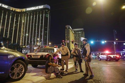 Police officers stand at the scene of a shooting near the Mandalay Bay resort and casino on the Las Vegas Strip, Sunday, Oct. 1, 2017, in Las Vegas.