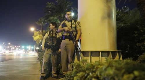 Police officers take cover near the scene of a shooting on the Las Vegas Strip
