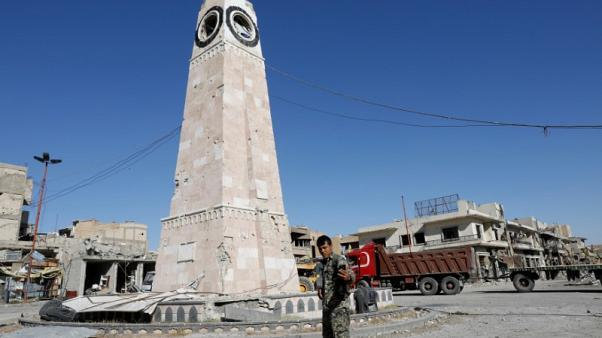 A fighter of Syrian Democratic Forces takes a selfie at a clock tower in Raqqa, Syria October 18, 2017.