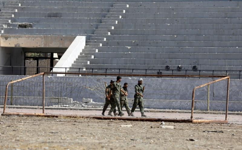 Fighters of Syrian Democratic Forces walk at the stadium in Raqqa, Syria October 18, 2017