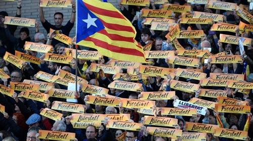 A Catalan pro-independence Estelada flag waves above the crowd of protesters holding placards reading Freedom at a Barcelona demonstration calling for the release of jailed separatist leaders.