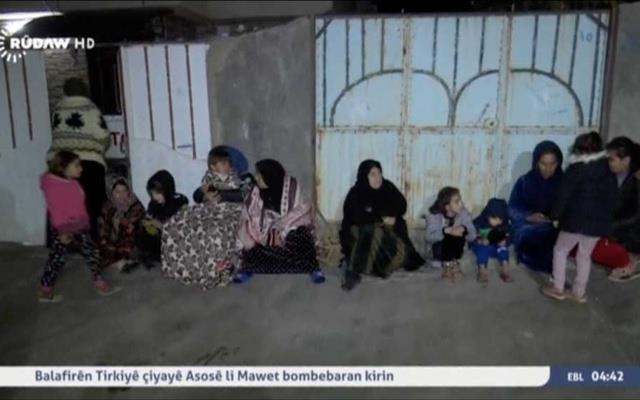 People sit on the pavement after an earthquake at an unknown location in Iraq in this still image taken from video Nov 13, 2017. Rudaw TV