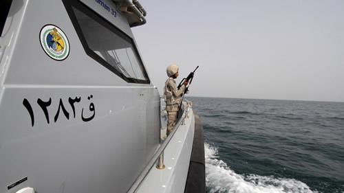 A Saudi border guard watches as he stands in a boat off the coast of the Red Sea on Saudi Arabias maritime border with Yemen, near Jizan April 8, 2015