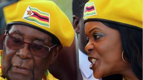 President Robert Mugabe listens to his wife Grace Mugabe at a rally of his ruling ZANU-PF party in Harare, Zimbabwe, November 8, 2017.