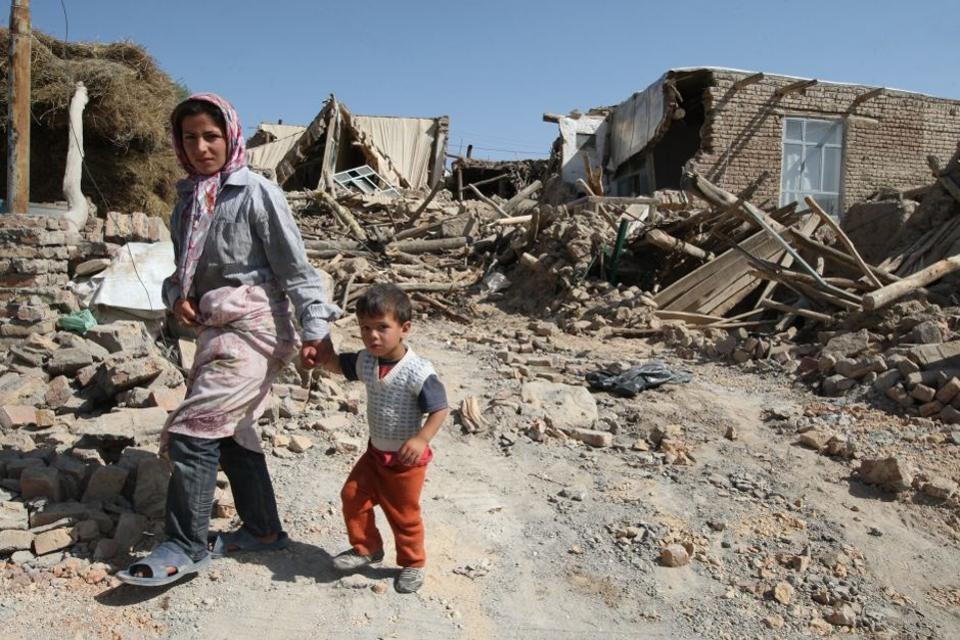 Iranian residents walk among the rubble of destroyed houses in a village after the quakes.