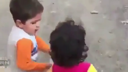 The child in the video appears heading for a truck distributing food, while holding his friend's hand.