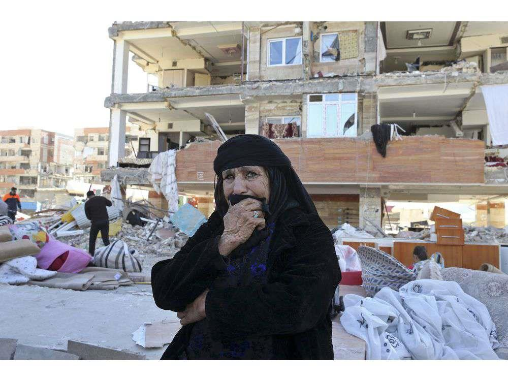An earthquake survivor weeps as she sits in front of damaged buildings, in a compound which was built under the Mehr state-owned program, in Sarpol-e-Zahab in western Iran, Tuesday, Nov. 14, 2017.