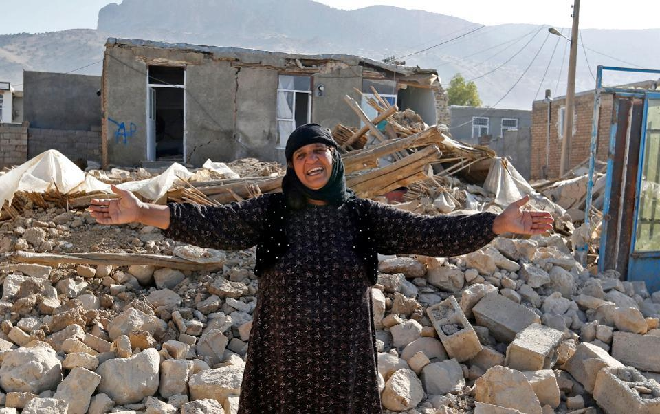 A picture taken on November 15, 2017 shows an Iranian woman gesturing next to the rubble of her home in Kouik village near to Sarpol-e Zahab, two days after a 7.3-magnitude earthquake struck Iran's western Kermanshah