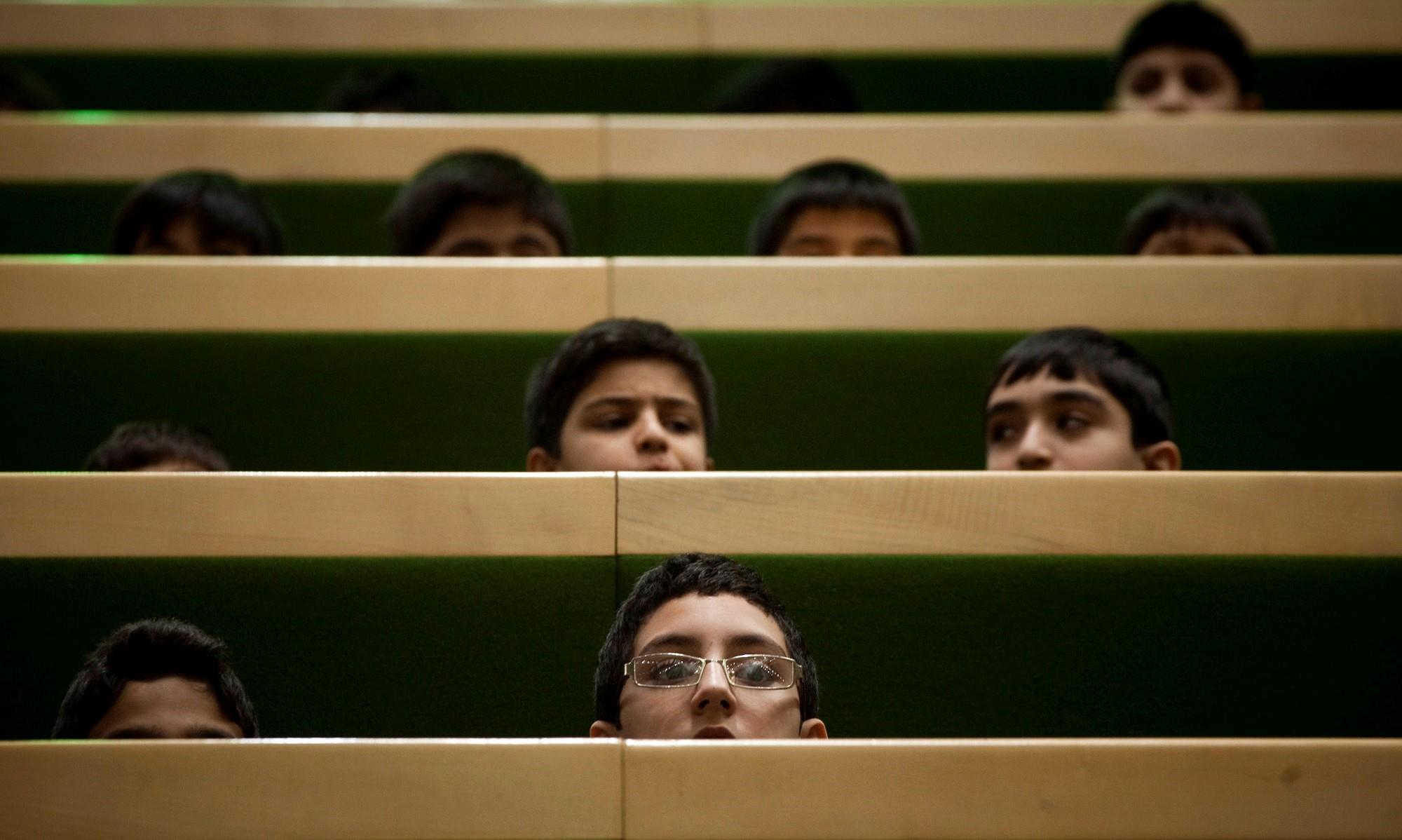 Schoolboys attend a session of the Iranian parliament in Tehran on December 11, 2011.