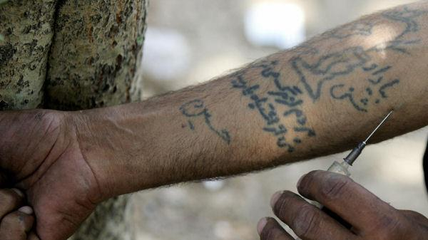 An Iranian drug addict injects himself with heroin in a park in Tehran