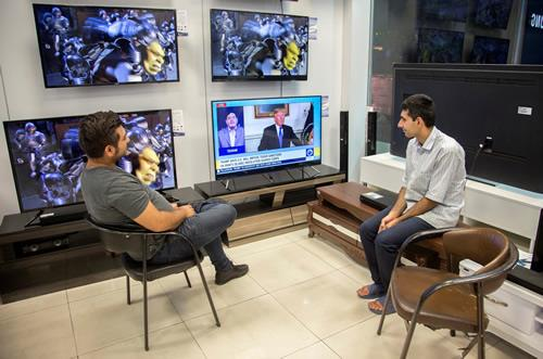 Men watch a television broadcast of US President Donald Trump's speech, in Tehran on October 13, 2017.