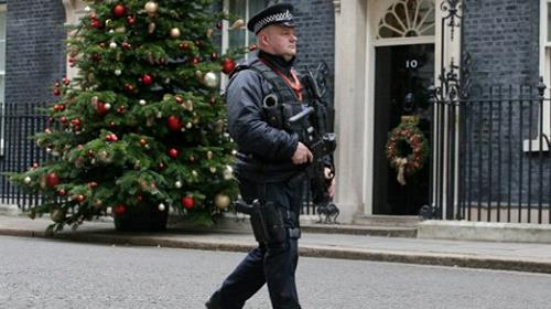 An armed police carries his automatic weapon as he walks on patrol outside 10 Downing Street in central London on December 6, 2017