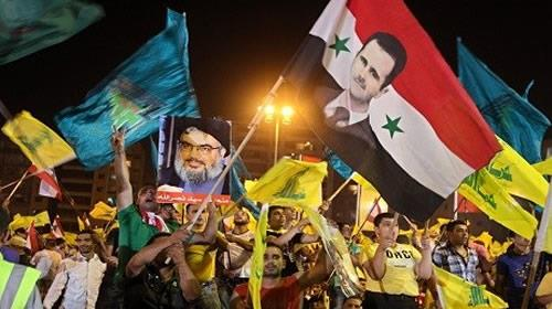 Demonstrators hoist Syrian regime, Iranian and Hezbollah flags