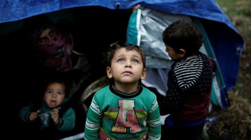 A Syrian refugee boy stands in front of his family tent at a makeshift camp for refugees and migrants next to the Moria camp on the island of Lesbos, Greece, November 30, 2017
