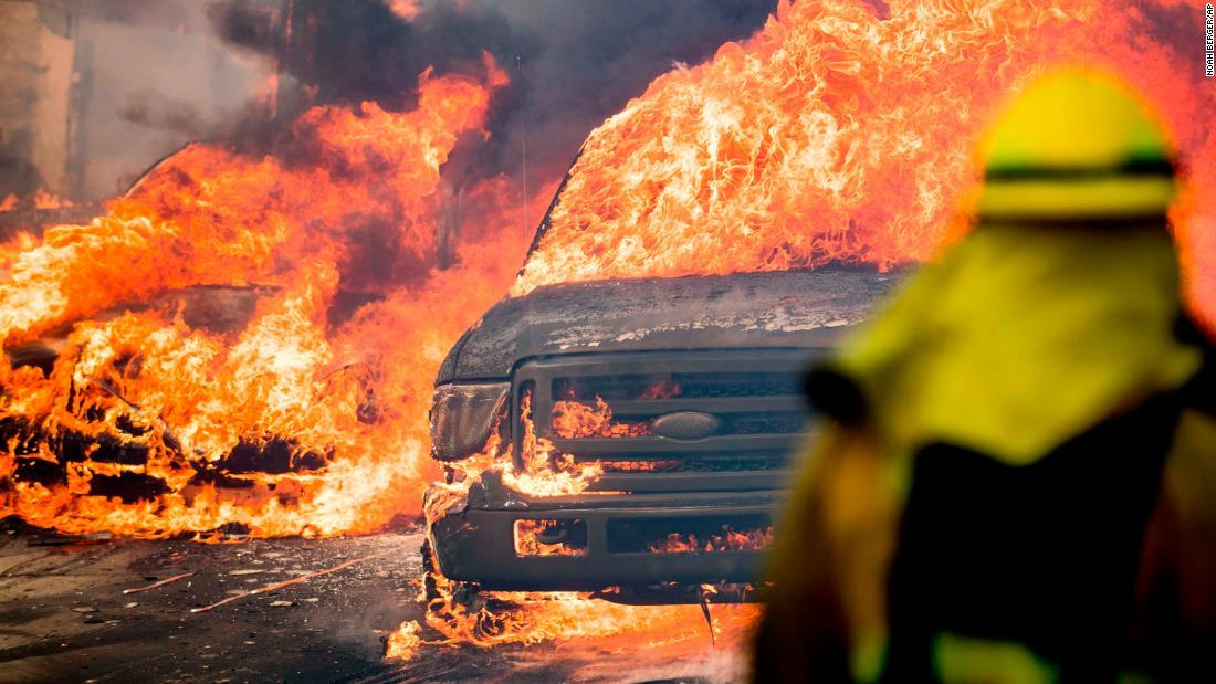 Flames consume vehicles in Ventura on Tuesday, December 5, as wildfires spread in Southern