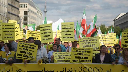 Activists in Berlin hold banners reading 'The people responsible for 1988 massacres need to be brought to court', on September 3, 2016