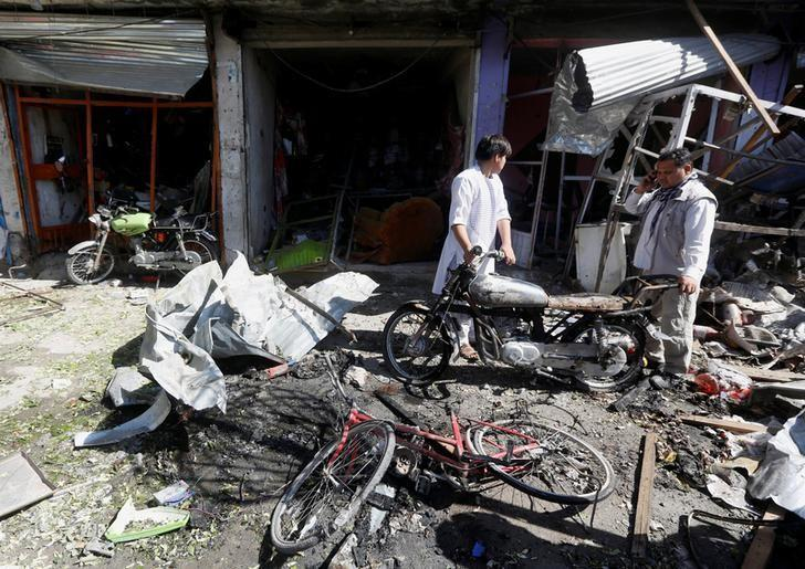 Afghan shopkeepers collect reamains in front of a shop after a suicide attack in Kabul, Afghanistan. July 24, 2017