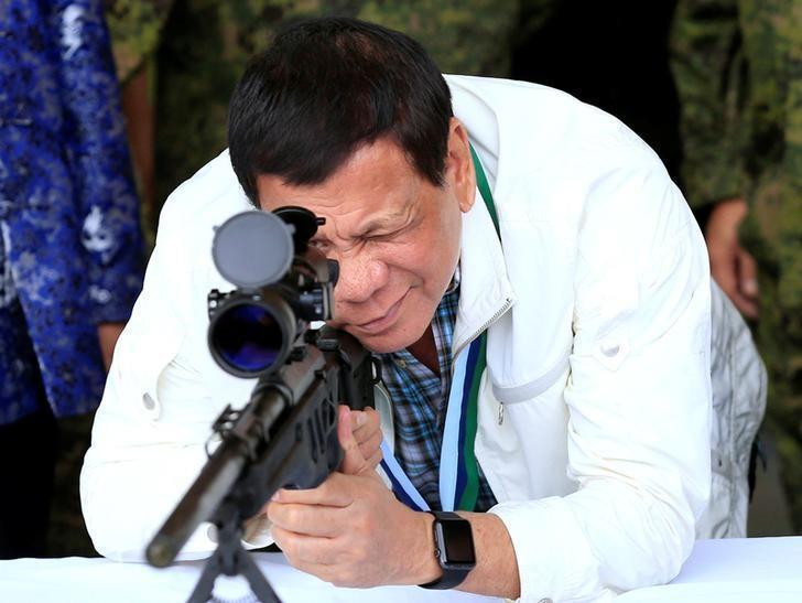 Philippines President Rodrigo Duterte checks the scope of a 7.62mm sniper rifle