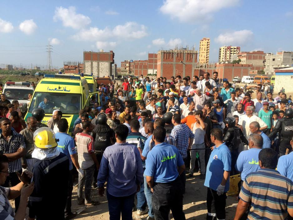 Egyptians and security personnel are seen at the site of a crash where two trains collided near the Khorshid station in Egypt's coastal city of Alexandria