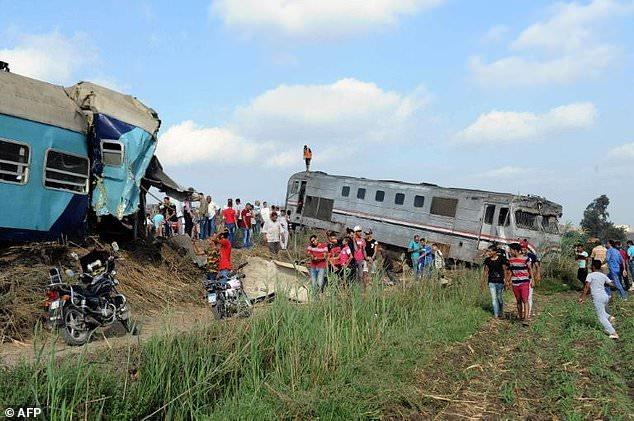 People gather at the site of a train collision near Egypt's Mediterranean city of Alexandria