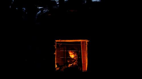 A Palestinian woman is seen from the window of her kitchen as she uses a candle light to prepare food during power cut in Beit Lahiya town in the northern Gaza Strip July 13, 2017