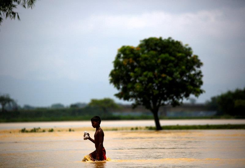 A boy walks along the flooded area in Saptari District, Nepal August 14, 2017.