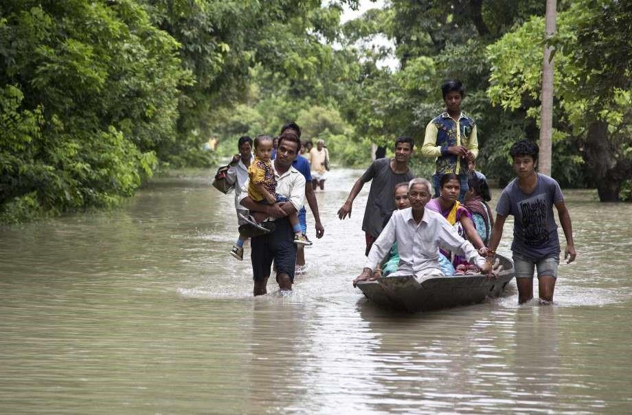 Commuters wade through flood waters on a road in Murkata village east of Gauhati