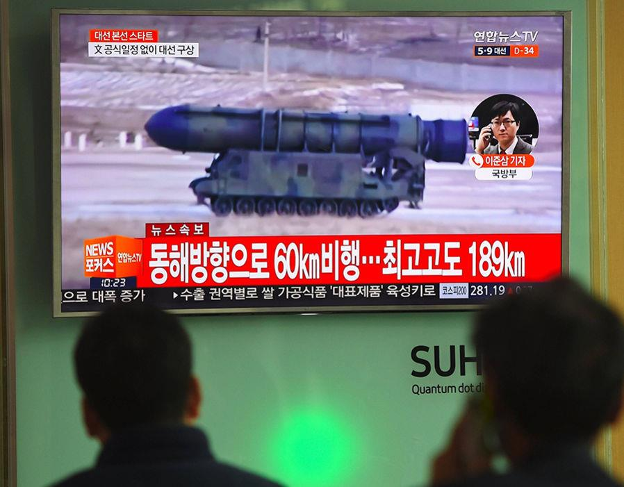 People watch a television news showing file footage of a North Korean missile launch