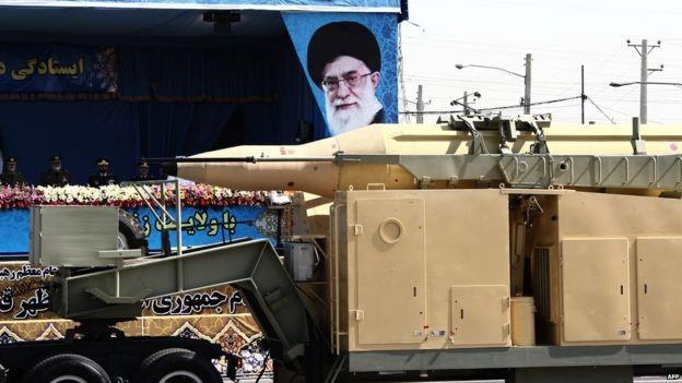 A military lorry carries a Qadr medium-range missile past portraits of Iran's Supreme Leader