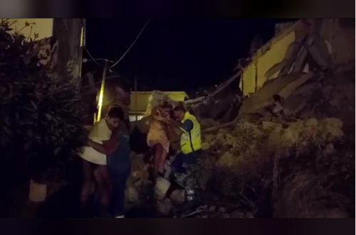 A woman is helped out of debris and rubble after an earthquake hit the island of Ischia, off the coast of Naples, Italy August 21, 2017, in this still image taken from video