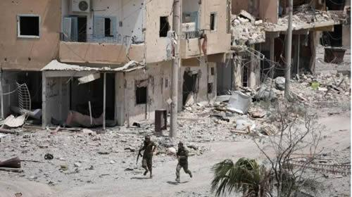 Fighters from Syrian Democratic Force (SDF) walk past damaged buildings in Raqqa city, Syria July 28, 2017.