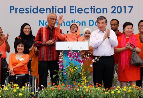 Halimah Yacob addresses supporters beside her husband Mohammed Abdullah Alhabshee in Singapore on September 13, 2017.