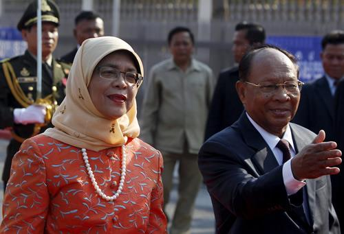 Halimah Yacob (L) inspects the honor guard, accompanied by Cambodia's President of the National Assembly Heng Samrin (R) during an official welcoming ceremony in Phnom Penh on May 7, 2015.
