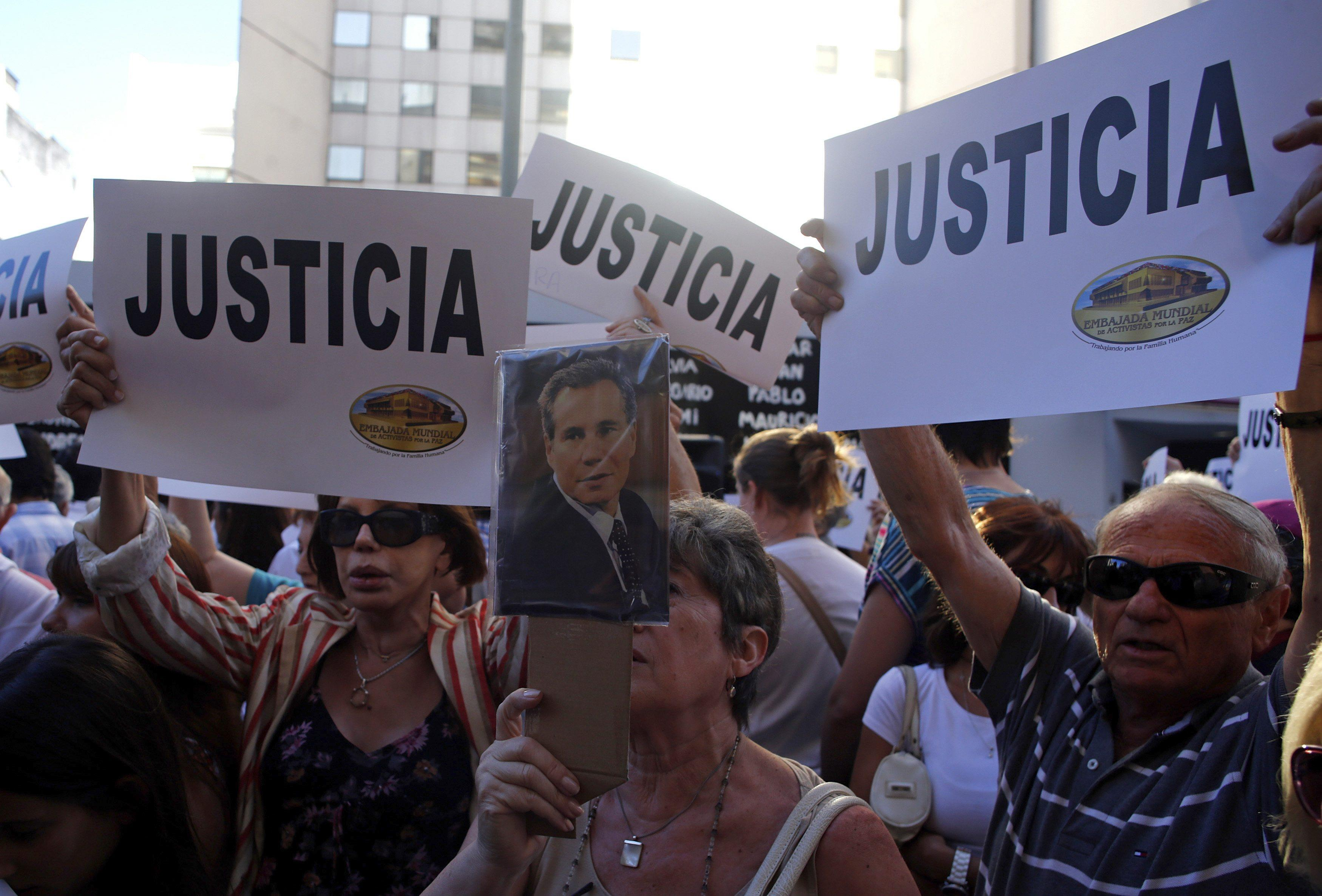 A woman holds up a picture of the late Argentine prosecutor Alberto Nisman during a demonstration Wednesday in Buenos Aires during a demonstration over his death.