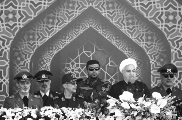Iranian regime President Hassan Rouhani, second from right, speaks ahead of the start of the 2017 Sacred Defense Week military parade.