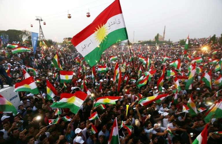 Iraqi Kurds fly Kurdish flags during an event to urge people to vote in the upcoming independence referendum in Arbil,