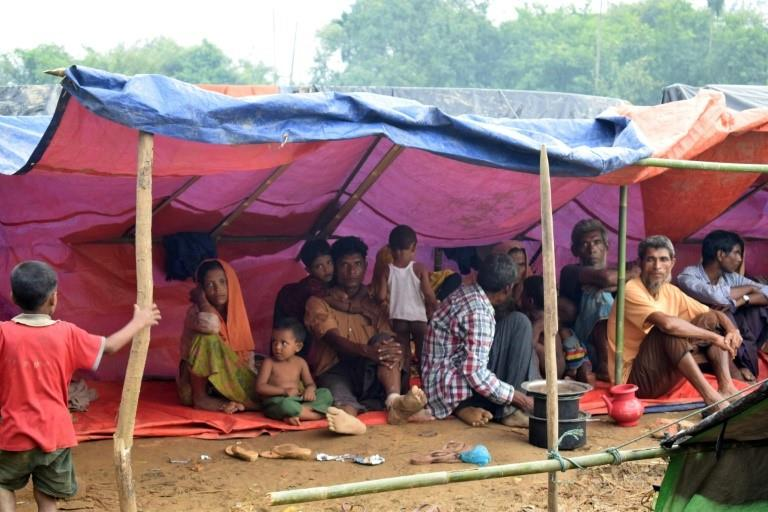 Rohingya refugees rest under a tent in a meadow in Ukhiya, Bangladesh