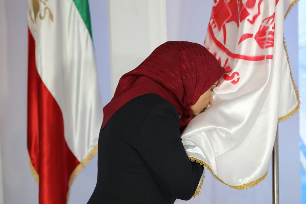 Ms. Zahra Merrikhi paying respect to the PMOI Emblem and Iranian flag