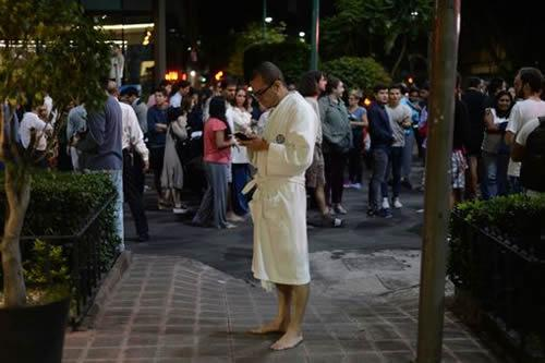 People gather on a street in Mexico City