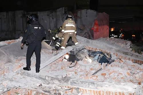 Rescuers stand amongst the rubble of a building