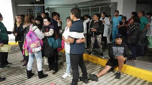 People embrace outside a hospital in Mexico City